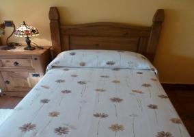 Dormitorio de la casa rural con colcha floral y muebles de madera