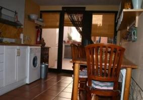 Cocina comedor con mesa de madera y lavadora