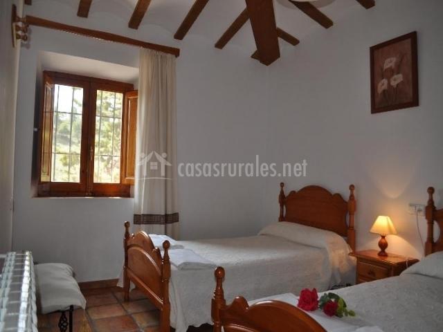 Habitación con dos camas individuales de paredes y colchas blancas y vigas de madera en el techo