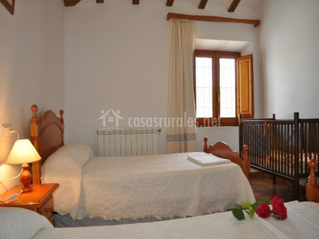 Habitación con dos camas individuales y cuna para bebés con paredes blancas y calefacción