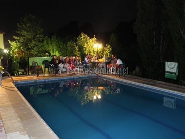 Imagen de la piscina por la noche con un grupo de huéspedes disfrutando de una reunión