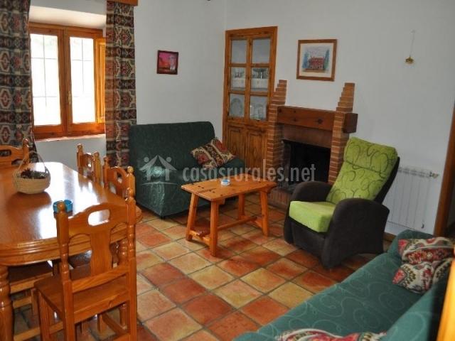 Salón de la casa rural con chimenea de leña y mesa de comedor de madera así como sofas y butaca