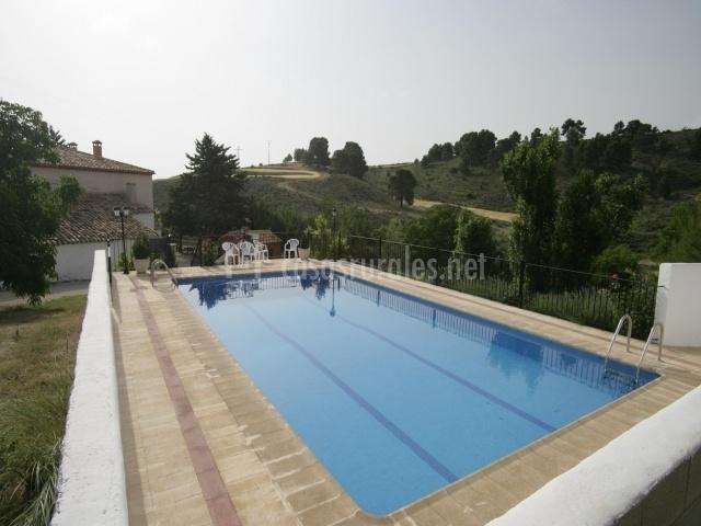 Imagen de la piscina con zona de solarium entre campos verdes y cielo despejado