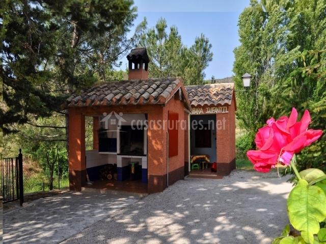 Vista de la zona de juegos infantiles con una pequeña cabaña y otra de las barbacoas del complejo rural