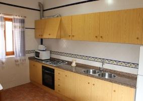 Cocina independiente de azulejs blancos y muebles de madera clara