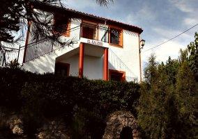Fachada principal de la entrada al alojamiento con paredes blancas