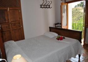 Habitación con cama de matrimonio y balcón con paredes blancas