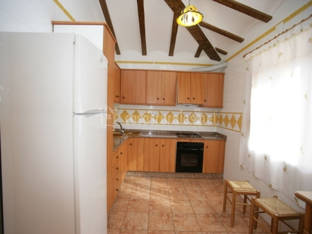 Cocina de la casa con muebles de madera y azulejos blancos