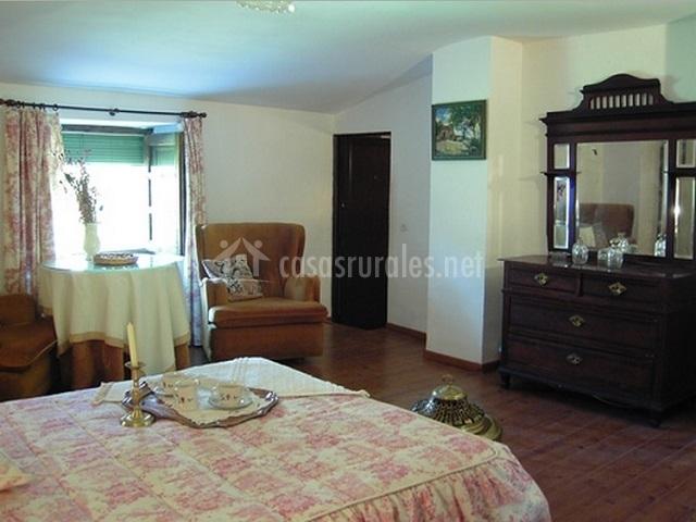 Dormitorio con mesa y butacas