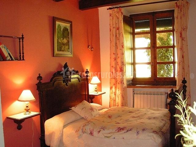 Dormitorio de matrimonio con ventana al jardín