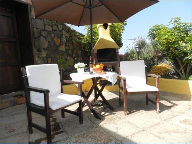 Mesa, sillas y barbacoa en el patio