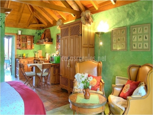 Salón comedor con sillones y paredes verdes