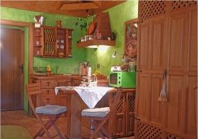 Cocina con mesa de comedor y muebles de madera