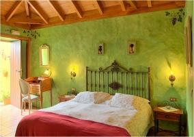 Detalle de la cama de matrimonio con pared verde