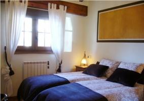 Dormitorio con camas individuales y ventana en la casa rural