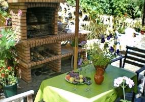 Mesa verde en el patio con barbacoa de ladrillo