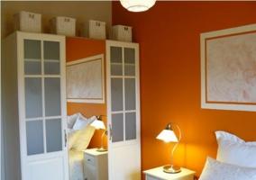 Dormitorio de matrimonio con armarios en blanco y paredes naranjas