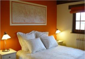 Dormitorio de matrimonio con edredón blanco y paredes naranjas