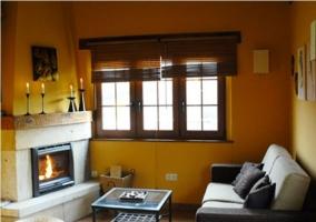 Salón con paredes amarillas, sofá y chimenea