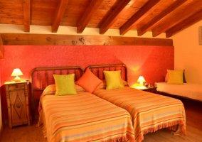 Dormitorio con camas individuales y techos de madera de la casa rural