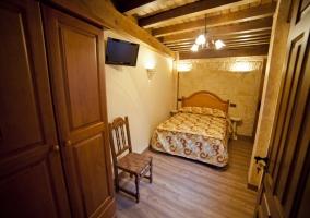 Dormitorio con TV y techos de madera