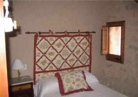 Dormitorio matrimonial con colcha blanca con detalles bordados en la casa rural
