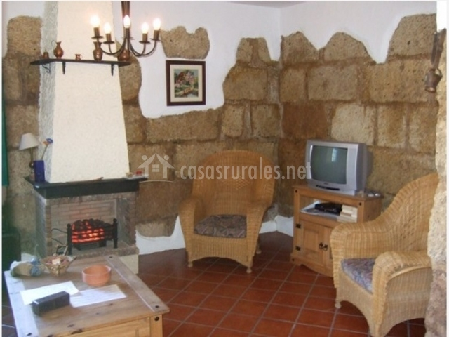 Butacas de mimbre de la sala de estar con chimenea de la casa rural