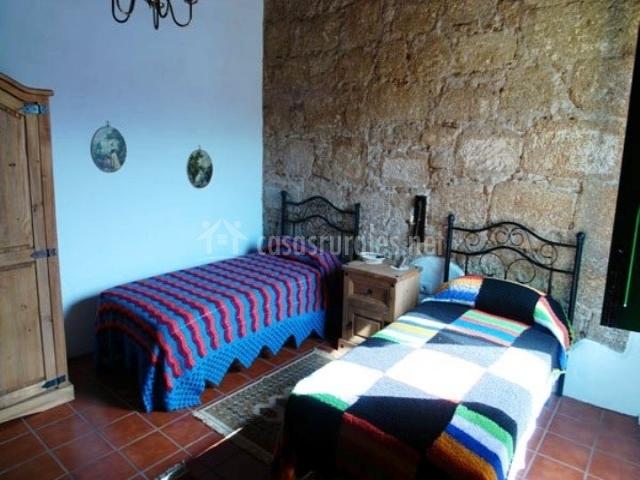 Dormitorio doble con 2 camas individuales y pared de piedra