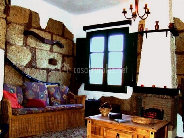 Sala de estar con paredes de piedra y chimenea de la casa rural