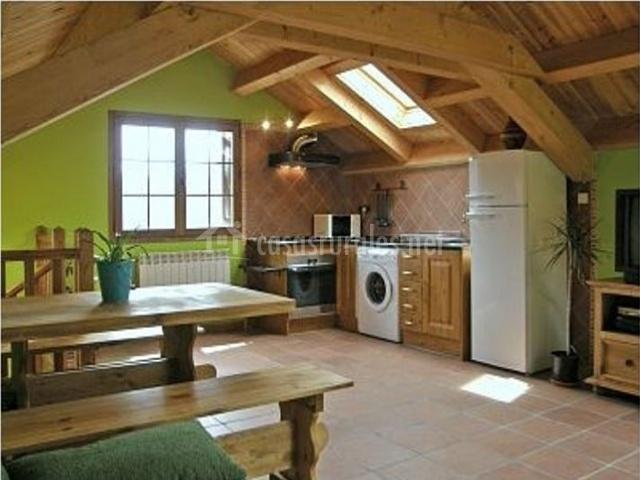 Cocina con mesa de comedor y bancos en madera