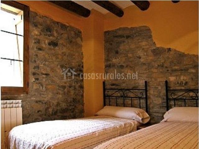 Dormitorio con camas individuales y paredes de piedra