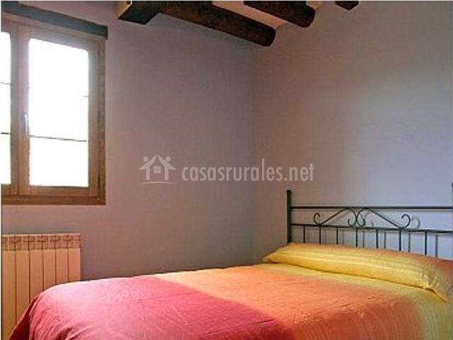 Dormitorio doble con colcha en tonos cálidos
