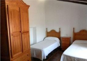 Dormitorio doble con camas individuales y armario de madera