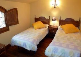 Habitación doble con camas individuales y ventanas de madera