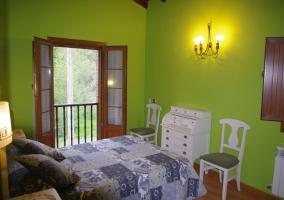 Dormitorio de matrimonio en verde con muebles blancos