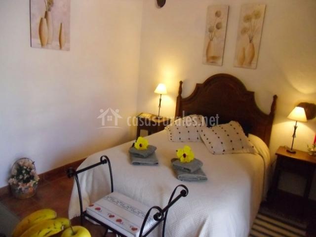 Habitación de matrimonio equipada con toallas y flores amarillas