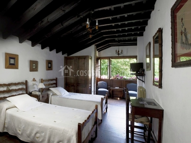 dormitorio doble con sillones y ventanales