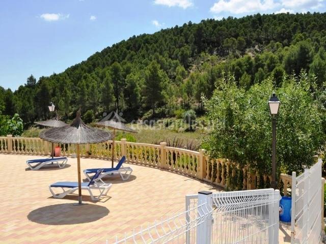 Zona de la piscina con sombrillas y hamacas