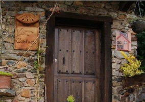 Acceso principal de la casa con puerta de madera