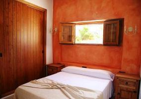 Dormitorio con pared de madera y estuco en naranja