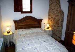 Dormitorio de matrimonio con columna de piedra
