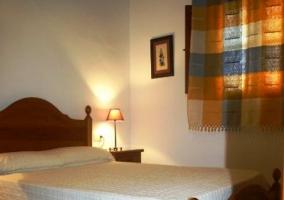 Dormitorio de matrimonio con cama blanca y cortinas de cuadros