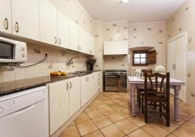 Cocina muy amplia con mesa y armarios