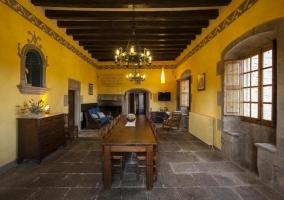 Comedor con chimenea una gran mesa y techos de madera con vigas