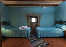 Dormitorio azul con 2 camas individuales estilo añejo