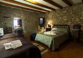 Dormitorio con 2 camas separadas y peredes revestidas de piedra