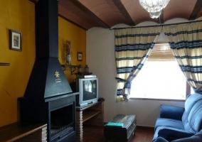Salón con sofás y techos rústicos