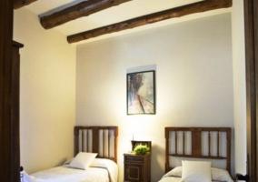 Dormitorio con dos camas individuales y toallas