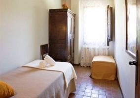 Dormitorio con dos camas individuales y vigas de madera en el techo