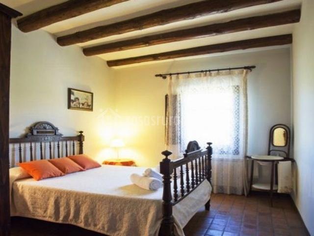 Dormitorio con cama de matrimonio y cojines naranjas